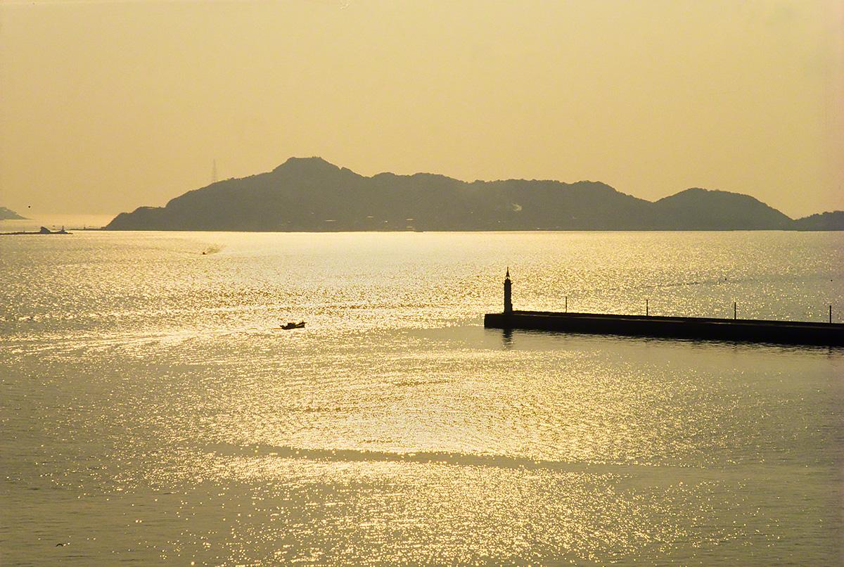 斜陽に輝く海と島影と灯台と船