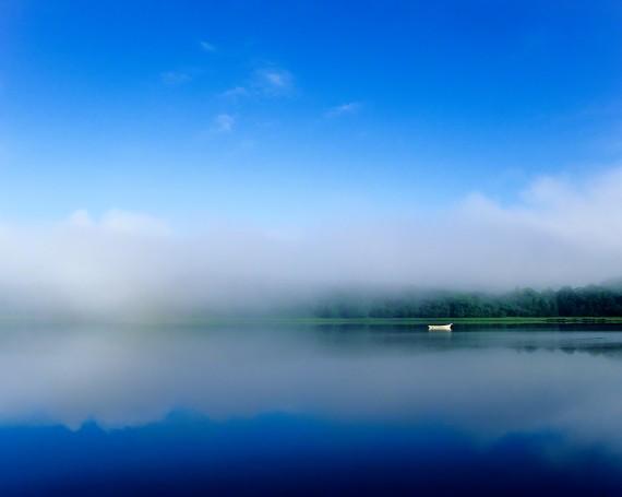 朝霧の湖面に浮かぶ白い船