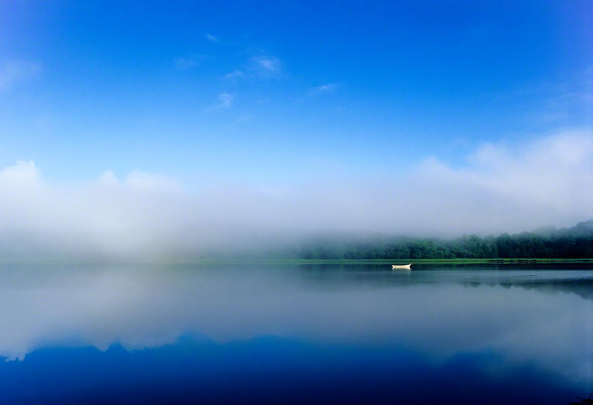 朝霧の湖面の白い船