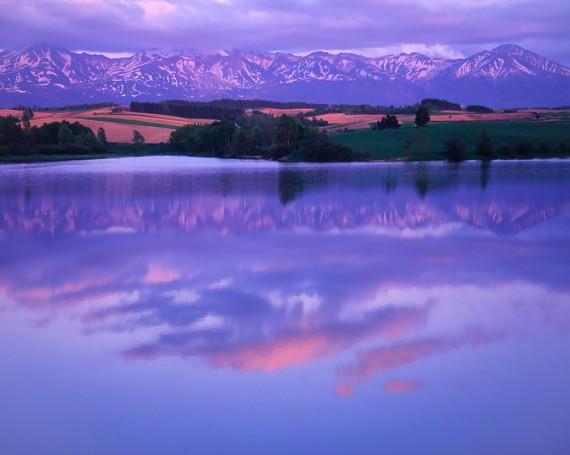 湖に映る夕焼雲と残雪の十勝連峰