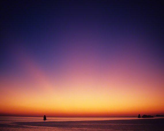 水平線の上の日没後の光芒と島影